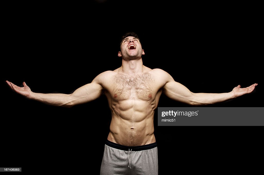 Topless man shouting with his arms outstretched : Stockfoto