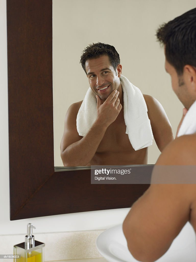 Topless Man Stands Looking at a Bathroom Mirror, Stroking His Chin : Stock Photo