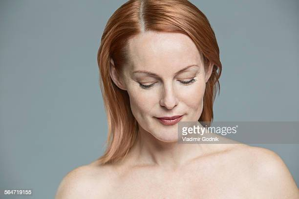 Topless shy woman against gray background