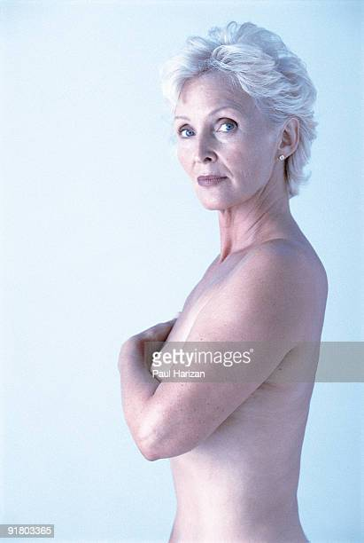 Topless woman covering breasts