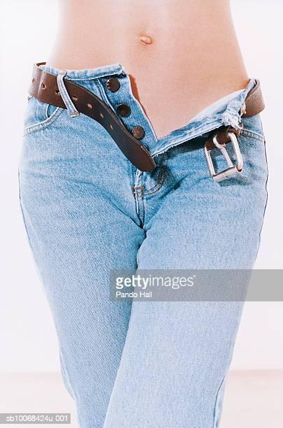Topless woman wearing denim jeans with open fly, studio shot, mid section