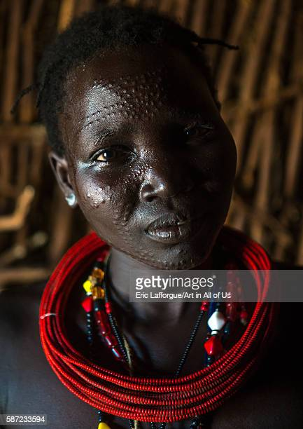 Toposa tribe woman with scarified face and red necklaces omo valley kangate Ethiopia on March 15 2016 in Kangate Ethiopia