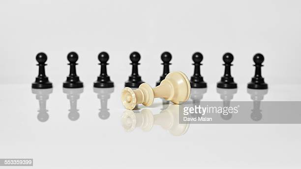 Toppled white queen in front of black pawns