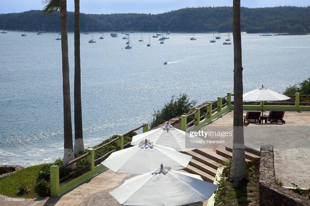 Tops of four white umbrellas on a patio overlooking boats in Tenacatita Bay; Costalegre, Jalisco, Mexico : Stock Photo