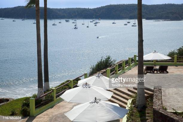 tops of four white umbrellas on a patio overlooking boats in tenacatita bay; costalegre, jalisco, mexico - timothy hearsum stock pictures, royalty-free photos & images
