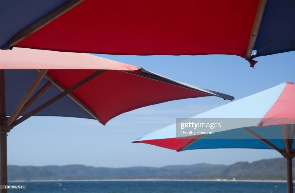 Tops of red and blue umbrellas in foreground, ocean, mountains and blue sky beyond; Tenacatita Bay, Costalegre, Jalisco, Mexico : Stock Photo