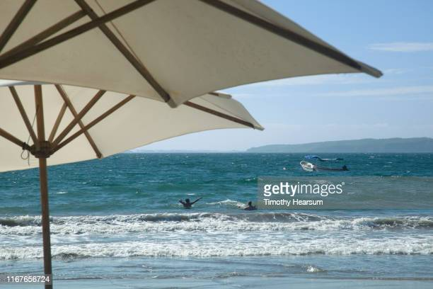 tops of two white umbrellas in foreground with two people playing in the ocean beyond - timothy hearsum stock pictures, royalty-free photos & images