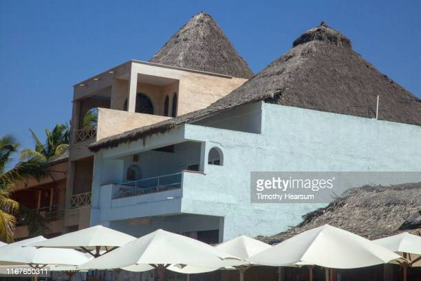 tops of white umbrellas in foreground, buildings with thatched roofs and blue sky beyond; costalegre, jalisco, mexico - timothy hearsum stock photos and pictures