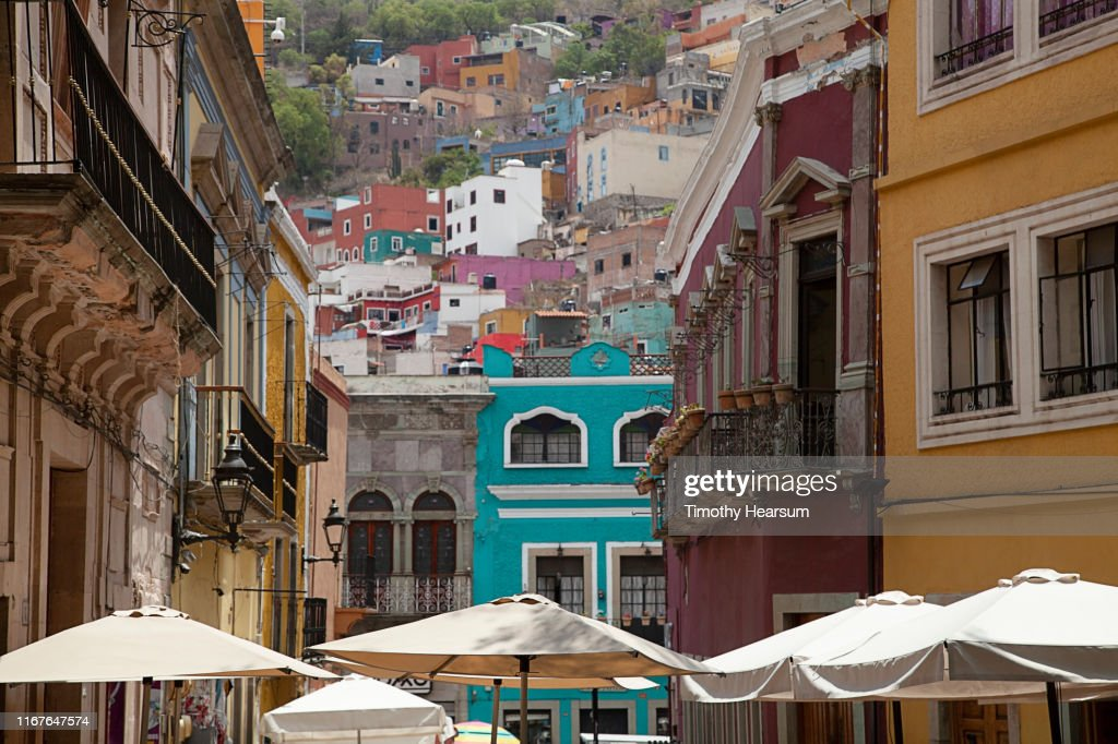 Tops of white umbrellas in foreground, colorful buildings on a hillside beyond; Guanajuato, Guanajuato State, Mexico : Stock Photo
