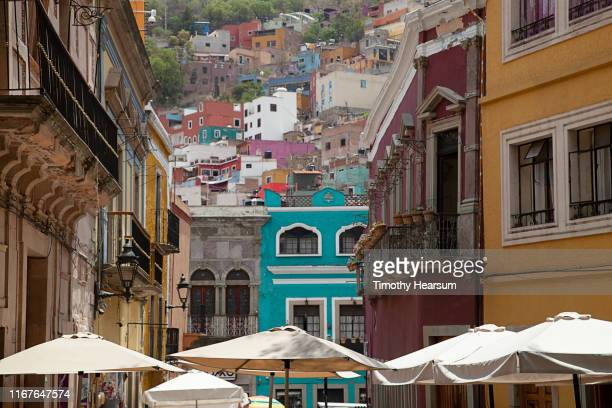 tops of white umbrellas in foreground, colorful buildings on a hillside beyond; guanajuato, guanajuato state, mexico - timothy hearsum stock photos and pictures