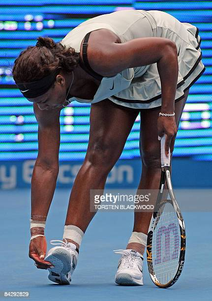 Topseeded Serena Williams of the USA checks the soles of her shoes after missing a return to thirdseeded Elena Dementieva of Russia during the...