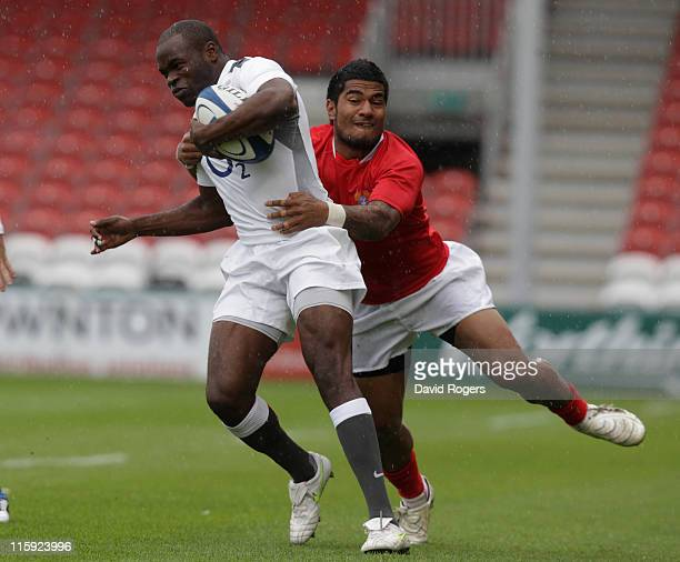 Topsy Ojo of England Saxons is held by Viliami Iongi during the Churchill Cup match between England Saxons and Tonga at Kingsholm on June 12, 2011 in...