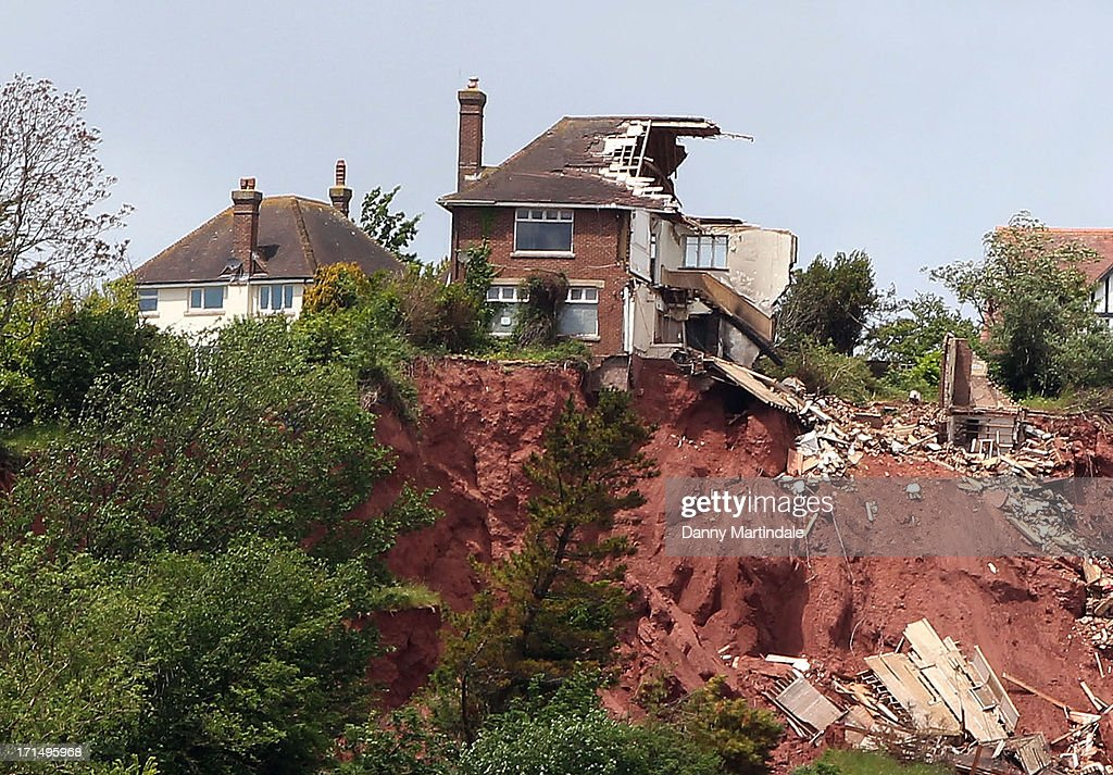 Tor Cottage, a four bedroom cliff-top home worth £400,000 (white house on the left) is seen on June 20, 2013 in Torquay, England. It is on the market for a mere £25,000 as it is at risk of falling into the sea the same way as the neighboring house has done.