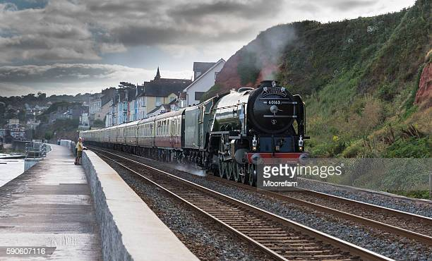 Torbay Express steam train speeding past Dawlish with onlookers