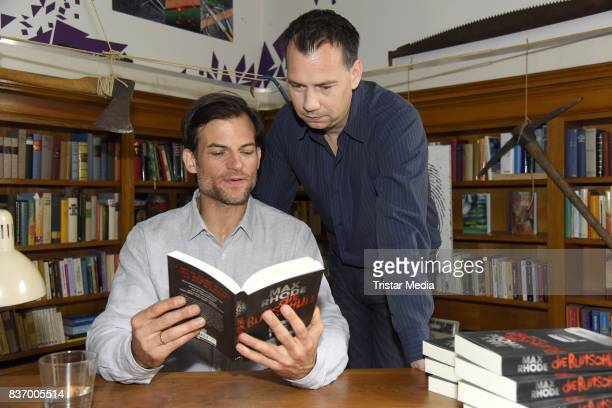 Torben Liebrecht and Sebastian Fitzek read a book on set during the RTL Event Movie 'Das Joshua-Profil' Photocall In Berlin on August 22, 2017 in...