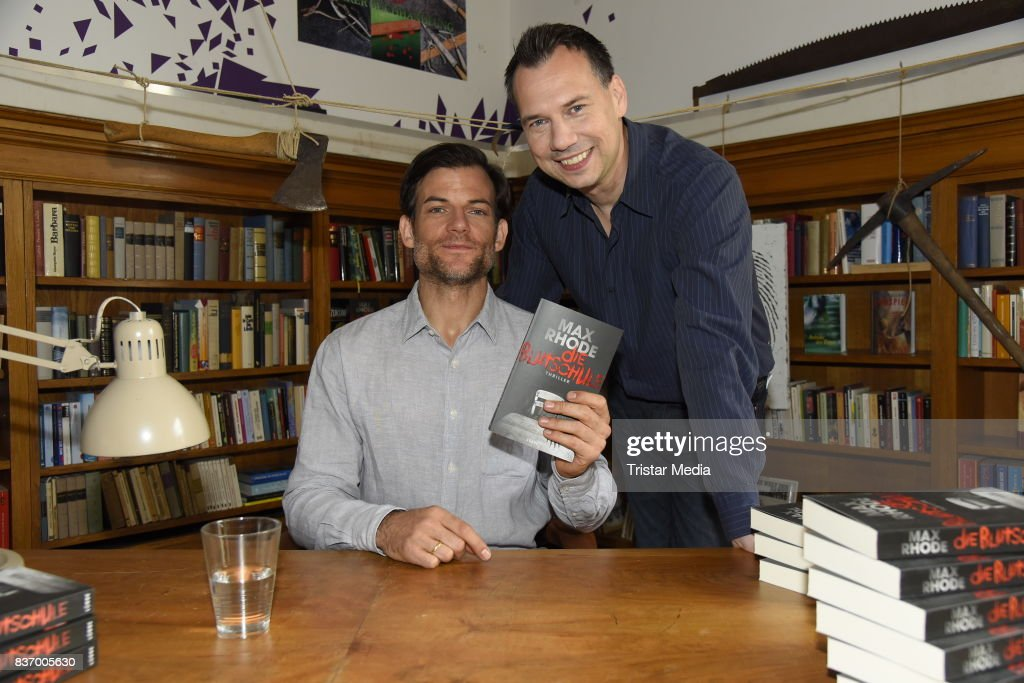 Torben Liebrecht and Sebastian Fitzek read a book on set during the RTL Event Movie 'Das Joshua-Profil' Photocall In Berlin on August 22, 2017 in Berlin, Germany.