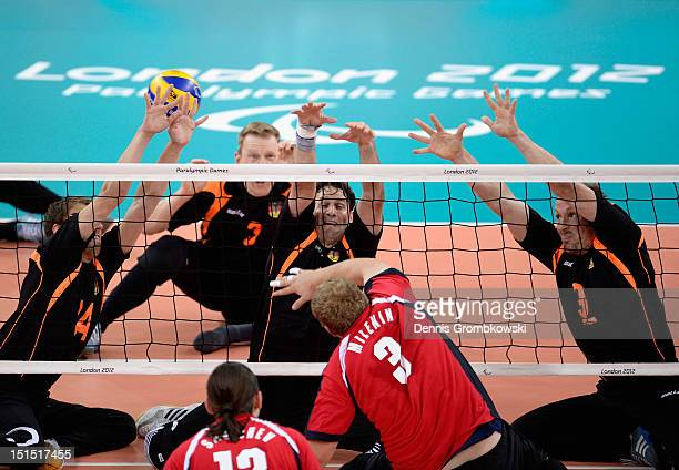 Torben Schiewe of Germany and teammates Heiko Wiesenthal and Thomas Renger block a ball by Viktor Milenin of Russian during the Men's Sitting...