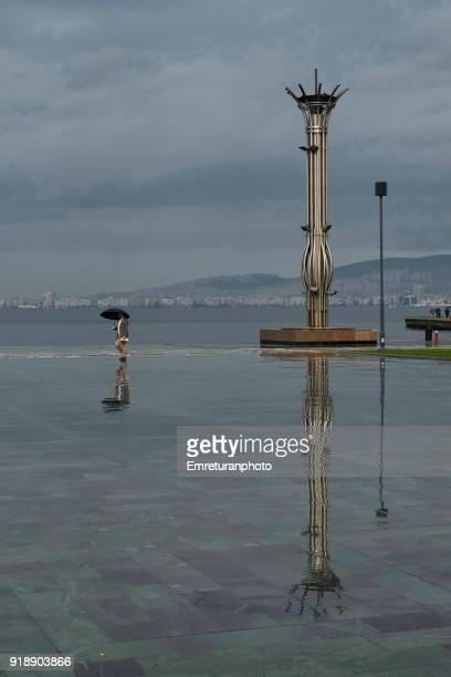 torch and walking man with reflections on wet floor on a rainy day,izmir. - emreturanphoto bildbanksfoton och bilder