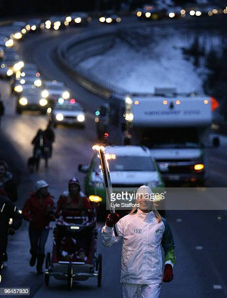 A torch barer carries the Olympic torch as it arrives in Whistler Village on February 5 2010 in Whistler British Columbia Canada