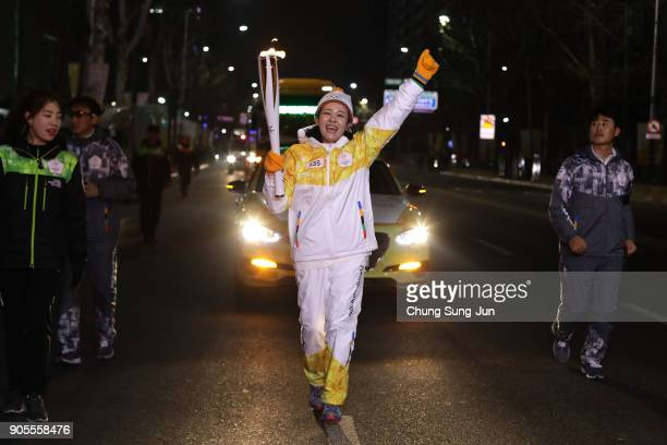 Torch bearer carries the PyeongChang 2018 Winter Olympics torch during the PyeongChang 2018 Winter Olympics torch relay on January 16, 2018 in Seoul,...