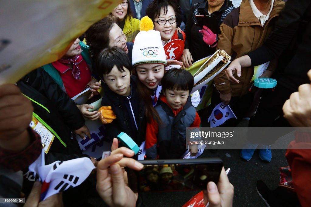 Torch bearer Kim Kun-Hee takes a selfie with fans 2018 Winter Olympics torch during the PyeongChang 2018 Winter Olympic Games torch relay on November 4, 2017 in Busan, South Korea.
