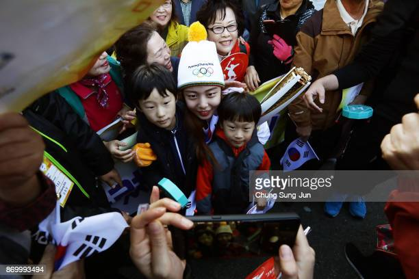 Torch bearer Kim KunHee takes a selfie with fans 2018 Winter Olympics torch during the PyeongChang 2018 Winter Olympic Games torch relay on November...