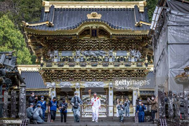 Torch bearer runs with the Olympic flame during the Tokyo Olympic Games Torch Relay at the Nikko Toshogu shrine on March 29, 2021 in Nikko, Tochigi,...