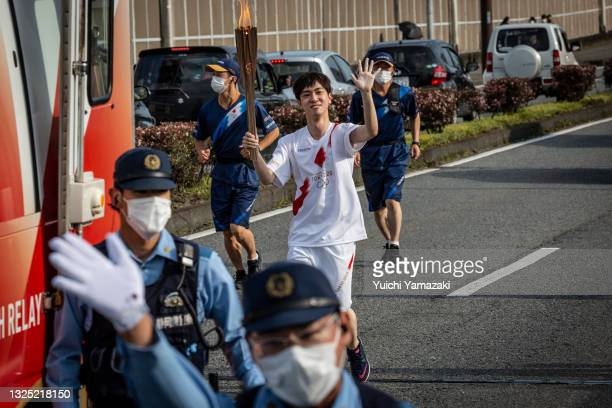 Torch bearer runs with the Olympic torch during the Tokyo Olympic Games Torch Relay on June 24, 2021 in Fuji, Japan. As the Olympic torch relay makes...
