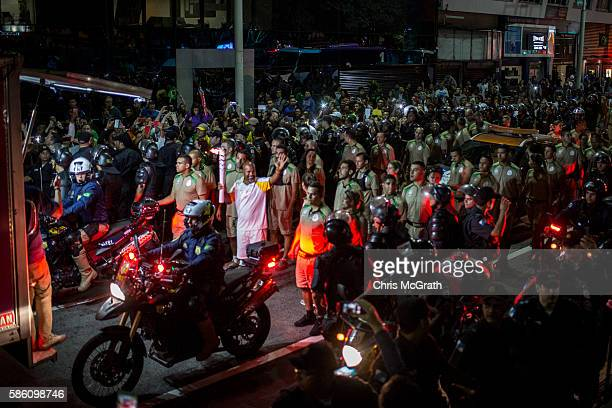 A torch bearer waves to the crowd surrounded by security as the torch relay passes through Copacabana ahead of the Rio 2016 Olympic Games on August 5...