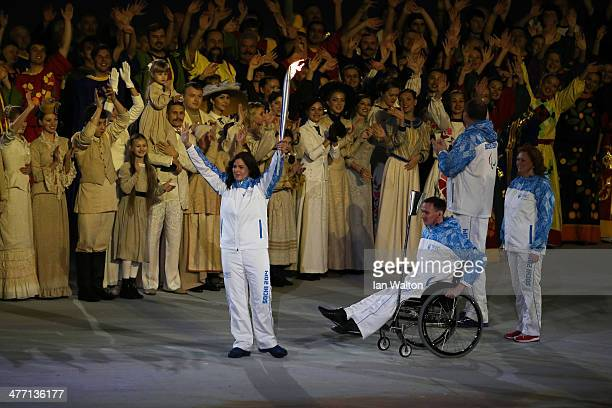 Torch bearers carry the flame into the arena during the Opening Ceremony of the Sochi 2014 Paralympic Winter Games at Fisht Olympic Stadium on March...