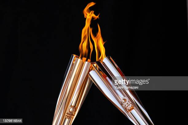 Torch bearers exchange the flame during the Olympic Torch Relay Celebration event on July 21, 2021 in Tokyo, Japan. As the Olympic torch relay makes...