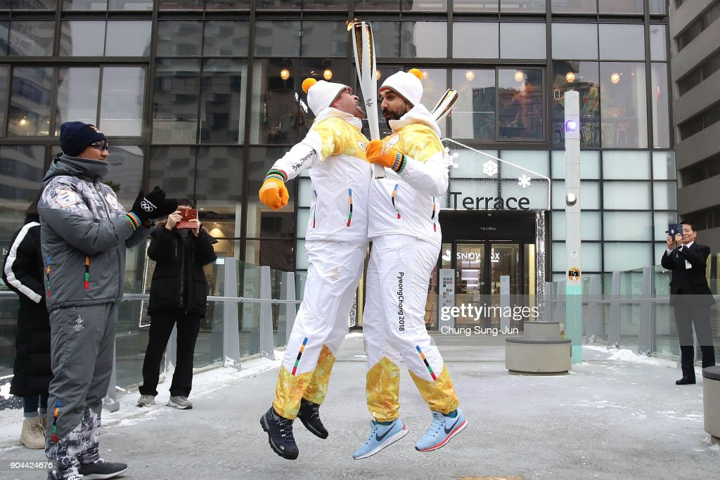Torch bearers hold the PyeongChang 2018 Winter Olympics torch during the PyeongChang 2018 Winter Olympic Games torch relay on January 13, 2018 in Seoul, South Korea.