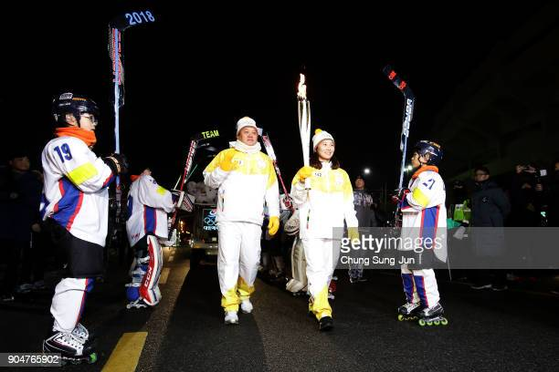 Torch bearers hold the PyeongChang 2018 Winter Olympics torch during the PyeongChang 2018 Winter Olympic Games torch relay on January 14 2018 in...