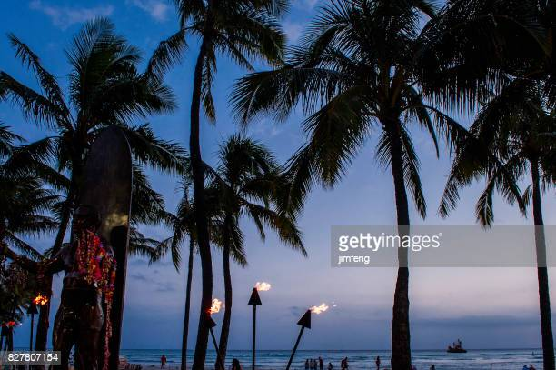 torch lighting in waikiki at dusk - duke stock pictures, royalty-free photos & images