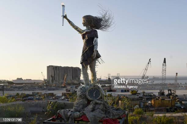 Torch lit on the hand of a symbolic sculpture is seen after protesters gather at Martyrs' Square to march towards Beirut Port where a massive...