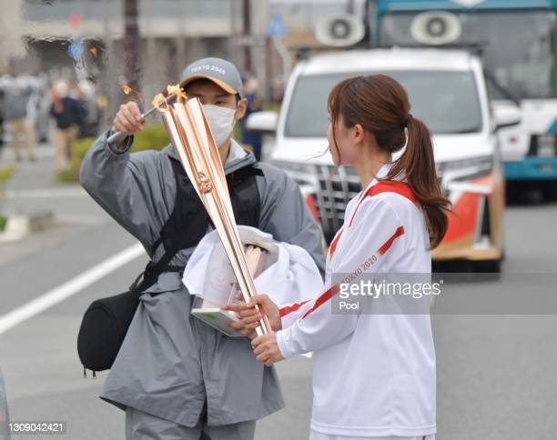 Torch relay staff relights the Olympic Flame to the torch as the flame went out during the Tokyo Olympic Games torch relay on March 25, 2021 in...