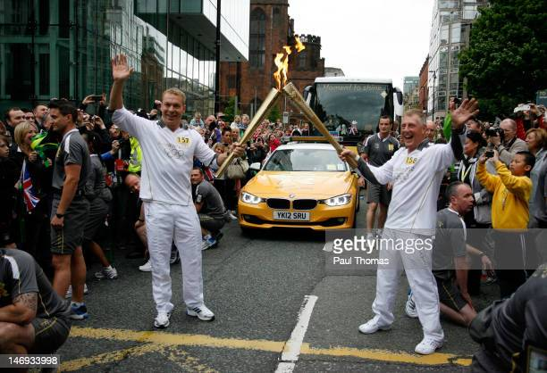 Torchbearer and British cyclist Sir Chris Hoy passes the Olympic Flame onto fellow torchbearer Geoff Cooke on the Torch Relay leg between Lytham St...