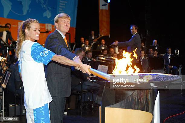 Torchbearer and Olympic swimmer Inge de Brujin lights a cauldron with the Olympic Flame during Day 19 of the ATHENS 2004 Olympic Torch Relay on June...
