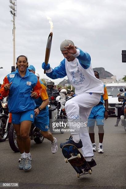 Torchbearer and professional skateboarder Robert Burnquist skates with the Olympic Flame during Day 10 of the Athens 2004 Olympic Torch Relay on June...