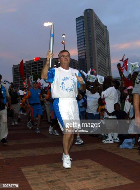 Torchbearer Billy Payne carries the Olympic Flame during Day 14 of the Athens 2004 Olympic Torch Relay on June 18 2004 in Atlanta Georgia The Olympic...