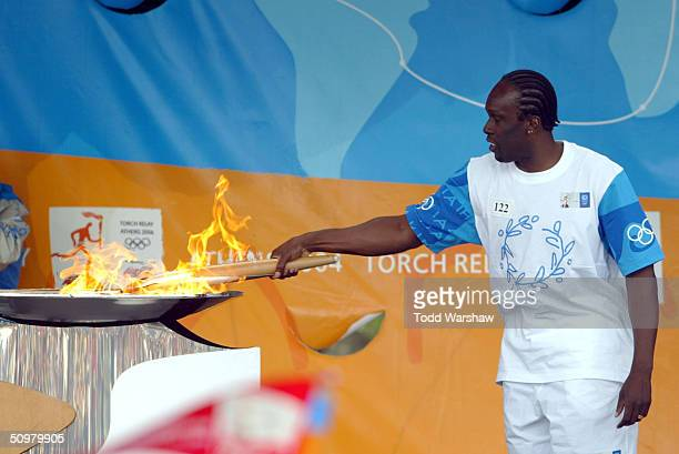Torchbearer Bruny Surin lights a cauldron with the Olympic Flame during Day 16 of the ATHENS 2004 Olympic Torch Relay on June 20 2004 in Montreal...