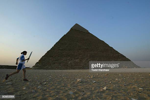 Torchbearer Doaa Elsaibb carries the Olympic Flame past the Pyramids during Day 8 of the Athens 2004 Olympic Torch Relay on June 11 2004 in Cairo...