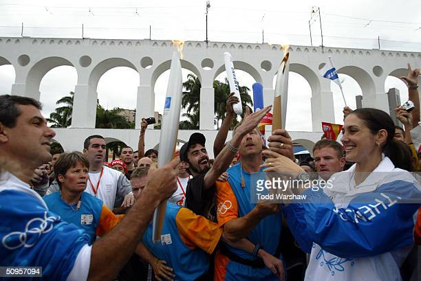 Torchbearer Fernanda Venturini passes the Olympic Flame to Jose Guimaraes in front of Aqueduto during Day 10 of the Athens 2004 Olympic Torch Relay...