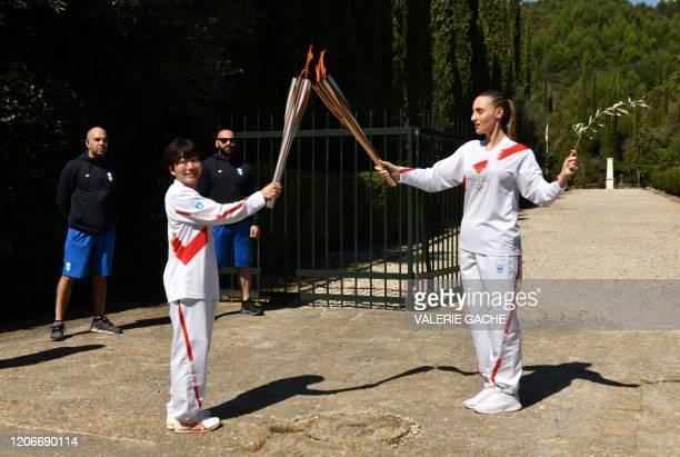 Torchbearer Greece's Anna Korakaki Rio 2016 gold medallist in the 25m pistol shooting gives the Olympic flame to Japan's Mizuki Noguchi Athens 2004...