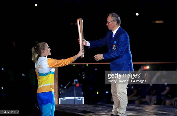 A torchbearer hands the baton to Chairman of Gold Coast 2018 Peter Beattie during the Opening Ceremony for the 2018 Commonwealth Games at the Carrara...