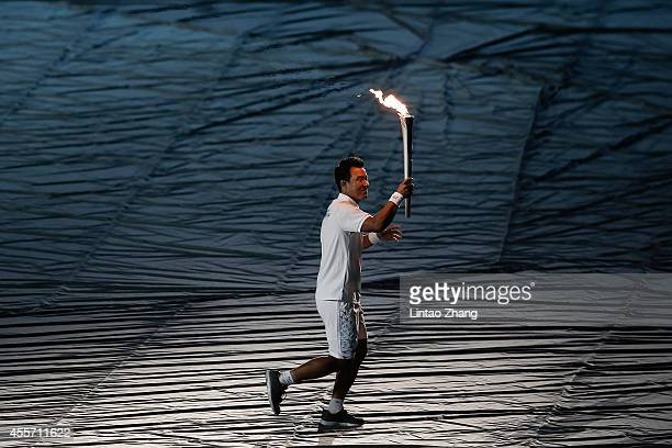 Torchbearer HyungTaik Lee of Korea enters the stadium during the Opening Ceremony ahead of the 2014 Asian Games at Incheon Asiad Stadium on September...