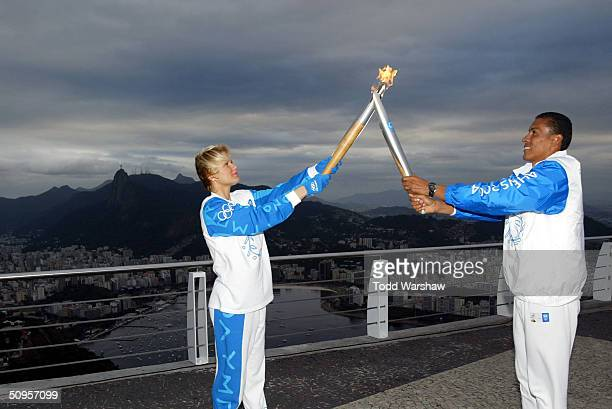 Torchbearer Joaquin Cruz passes the Olympic Flame to Xuxa Meneghel on top of Sugarloaf overlooking Rio de Janiero during Day 10 of the Athens 2004...