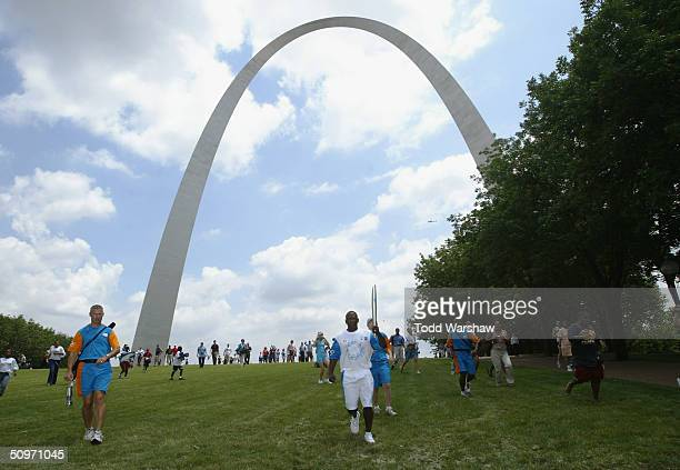 Torchbearer Joe Torry carries the Olympic Flame under the Gateway Arch during Day 13 of the ATHENS 2004 Olympic Torch Relay June 17 2004 in St Louis...