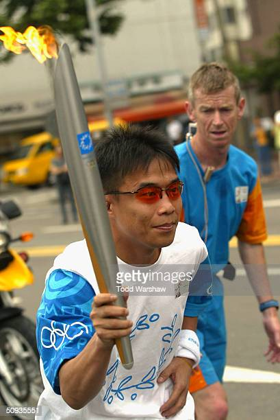 Torchbearer KwonHo Shim carries the Olympic Flame during Day 5 of the Athens 2004 Olympic Torch Relay on June 7 2004 in Seoul Korea The Olympic Flame...