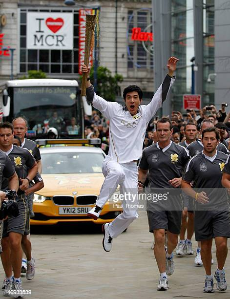 Torchbearer Leehom Wang of Taipei City carries the Olympic Flame on the Torch Relay leg between Lytham St Anne's and Manchester on June 23 2012 in...